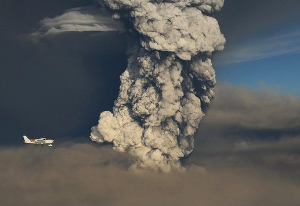 A small plane flies past a smoke plume from the eruption of the Grimsvotn volcano in southeastern Iceland