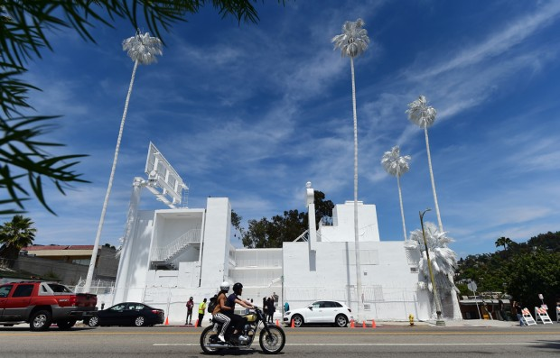 A couple on a motorcycle ride past 'Projection', a public art project of French installation artist Vincent Lamouroux, drawing attention with everything painted white to a forgotten Los Angeles landmark, Bates Motel, along Sunset Boulevard in Los Angeles, California on April 26, 2015. The motel, so nicknamed for its resemblance to the motel in Alfred Hitchcock's legendary thriller 'Psycho' has been in a state of disrepair for many years. AFP PHOTO / FREDERIC J. BROWN